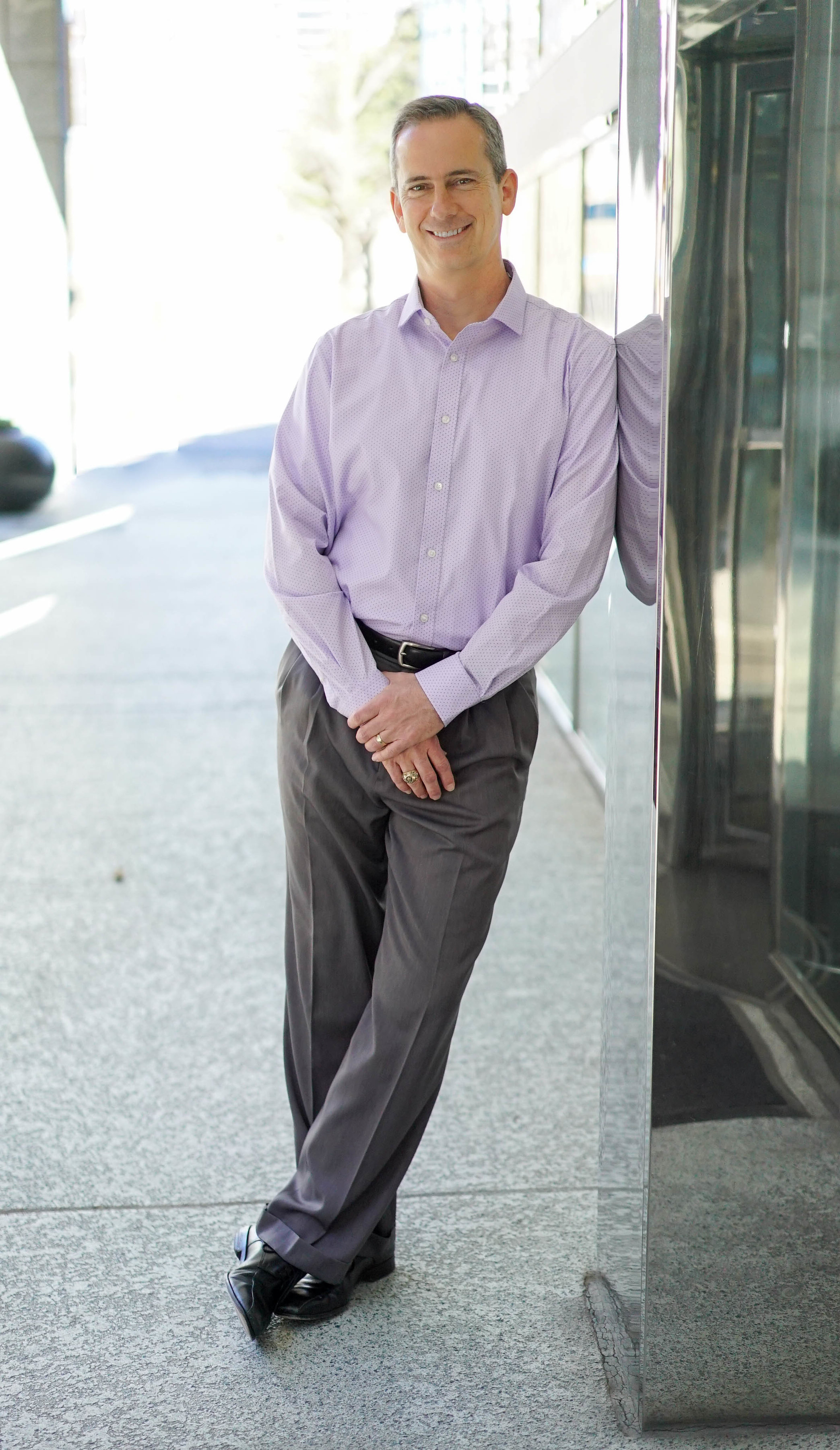A Caucasian male in a purple polo and gray slacks leaning against a wall smiling for a headshot