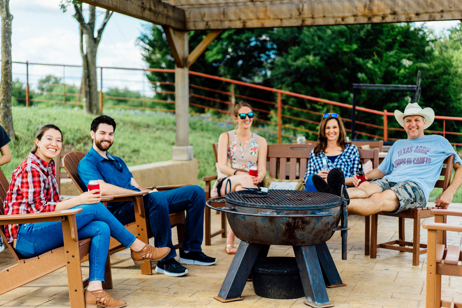 A group of males and females sitting in wooden chairs around a fire pit