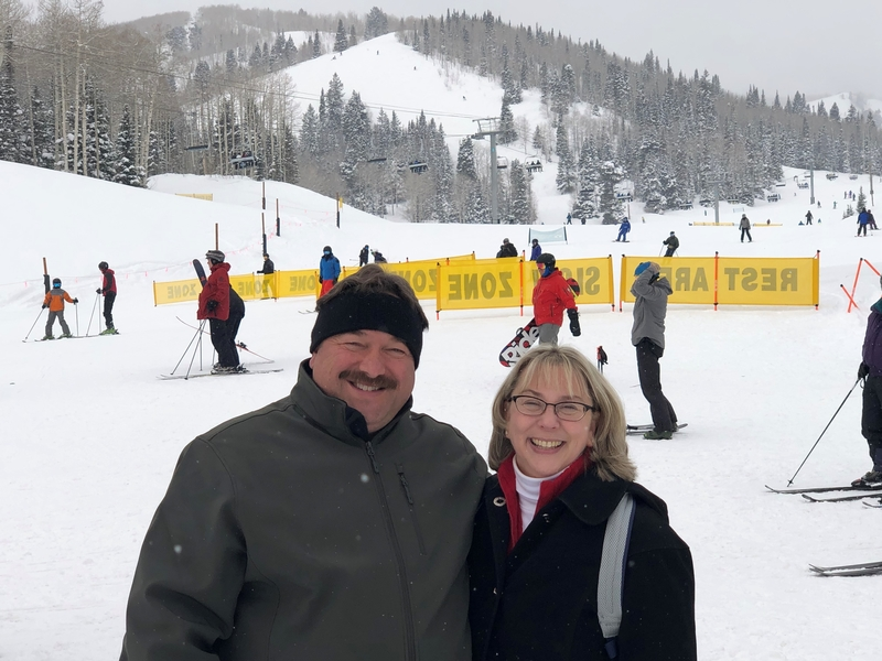 A Caucasian male and female posing for a photo in front of a snowy ski run at the base of the mountain