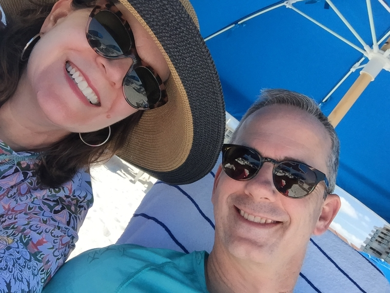 A Caucasian male and female taking a selfie under an umbrella at the beach