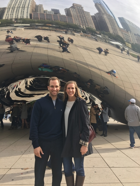 A Caucasian male and female posing for a photo in front of the Chicago bean