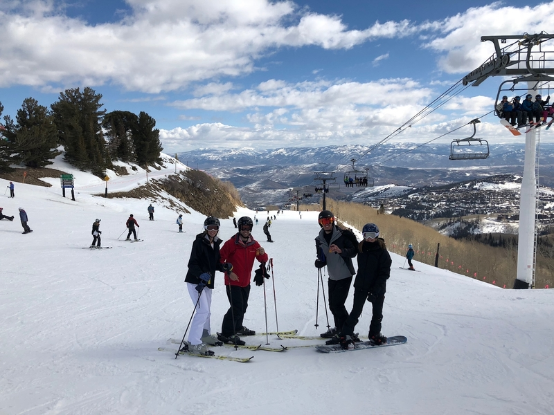 A group of males and females posing for a photo on a ski run in the mountains