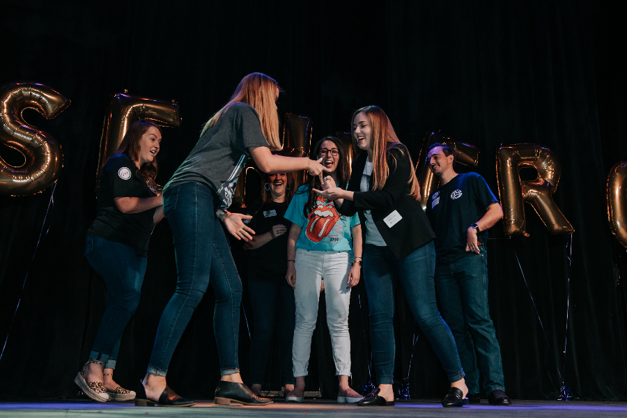 Two Caucasian females participating in a rock, paper, scissors competition on stage at an all-company meeting