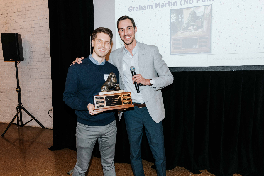 Two Caucasian males posing for a photo with a large trophy