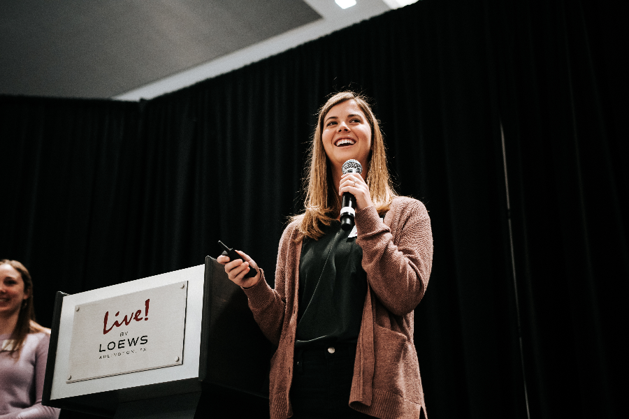 A Caucasian female holding a microphone presenting at an all-company meeting