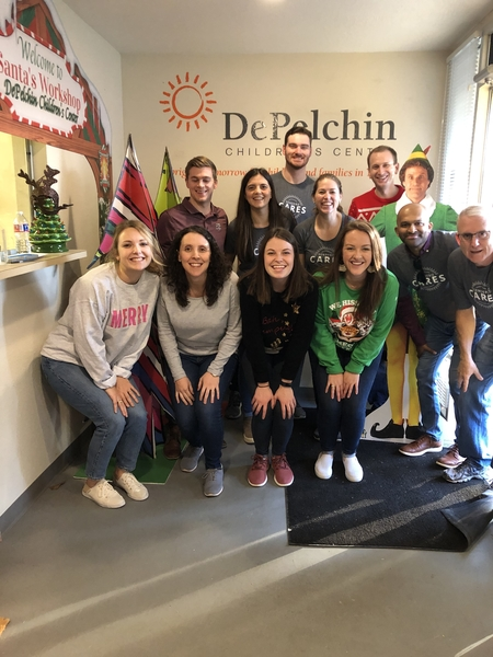 A group of males and females posing for a group photo in the DePelchin Children's Center lobby