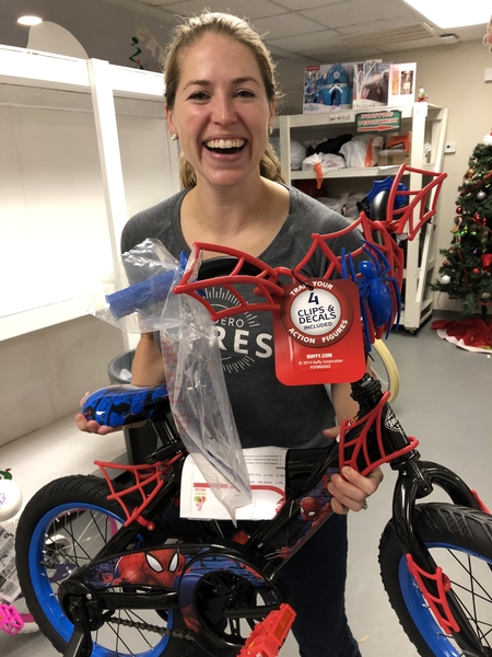A Caucasian female smiling while holding a children's bike