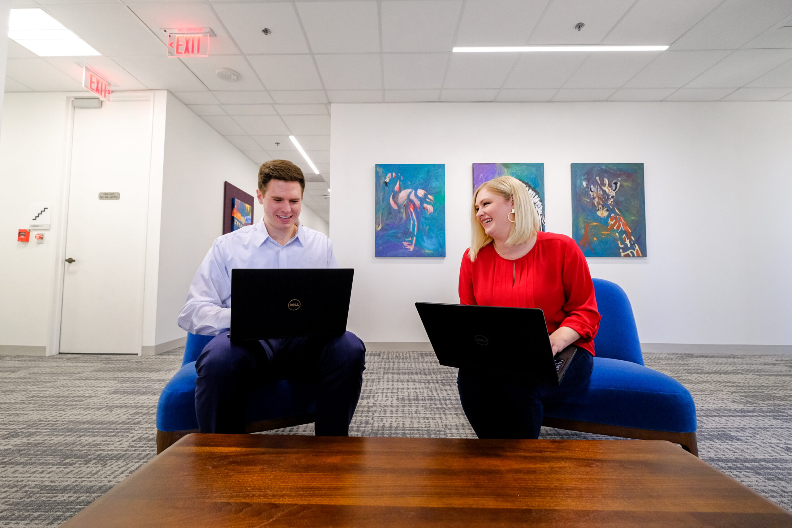 A Caucasian male and Caucasian female sitting in office chairs on laptops